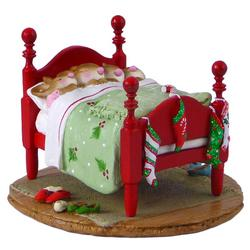 Four sleeping mice in one Christmas bed with stocking