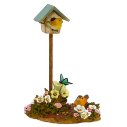 Birdhouse on a stick with two birds and flowers around base