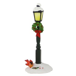 Street lamp in the snow with wreath under lamp and bird at base