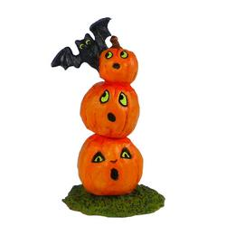 Three pumkins high with a bat on top