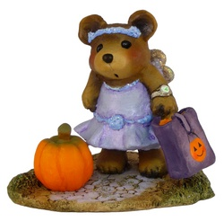 Bear in a party frock with wings and a candy bag, standing by a pumpkin