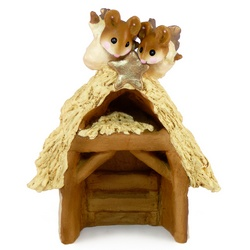 Wooden stable with thatched roof and two mouse angels on top
