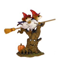 Two moce whitches fly their browm stick over an animate with a pumpkin at the base