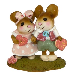Two young mice hold hands and Valentine's hearts