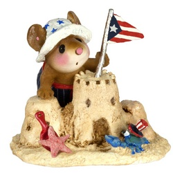 Boy mouse putting flag on sandcastle