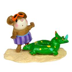Young mouse on a beach with a Dinosaur tube float