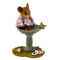 Young girl mouse sits on the edge of a bird bath bathing her feet whatching a butterfly