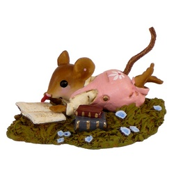 Young mouse lying in the grass reading a book