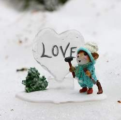 Boy mouse writes love on a heart shaped ice sculpture.