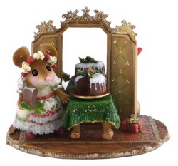 Hostess stands by large Christmas cake on a table in front of mirror screen