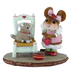 Young girl mouse with Valentine's heart looks at a kitten sitting on a chair