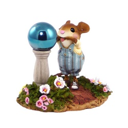 Child mouse pulls a face in front of a garden gazing ball