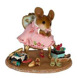 Young female mouse sitting on a chair surrounged by shoes