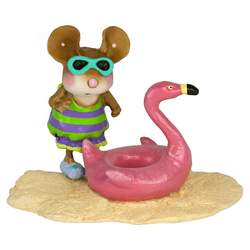 Young female mouse on a beach with a Flamomgo tube float
