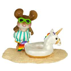 Young female mouse on a beach with a Unicorn tube float