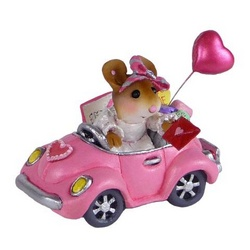 Girl in pink car with balloons holding a Valentine  card