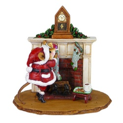 Santa in fromt of a fireplace fillling stockings
