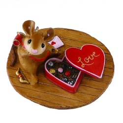 Young mouse sitting on floor eating a box Valentine's chocolates
