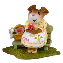Mother mouse holding a flower and  sitting on a wood banch with a basket of flowers