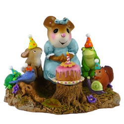 Lady mouse with bithday cake on a stump surrounded by animal freinds