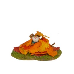 Young mouse covered in fall leaves