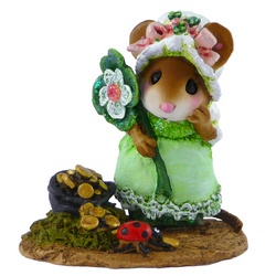 Young mouse in green dress hold a shamrock and looks at the treasure