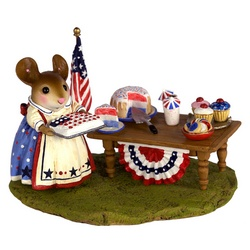Mother mouse standing in front of a garden table with RWB cakes and flags