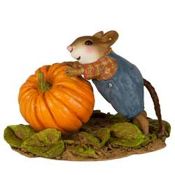 Boy mouse pushing large pumpkin