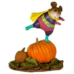 Girl superhero standing on a large pumpkin