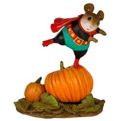 Boy mouse superhero standing on a large pumpkin