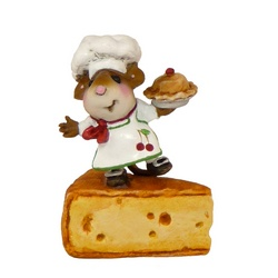 Tiny chef mouse standing on a slice of cheese holding a baked pie