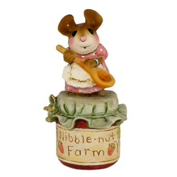 Tny mother mouse with wooden spoon standing on a jar of jam