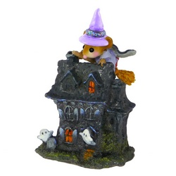 A Whitch pearers over the roof of miniture haunted house