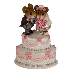 A miniature bride and groom stand on an elegant wedding cake.